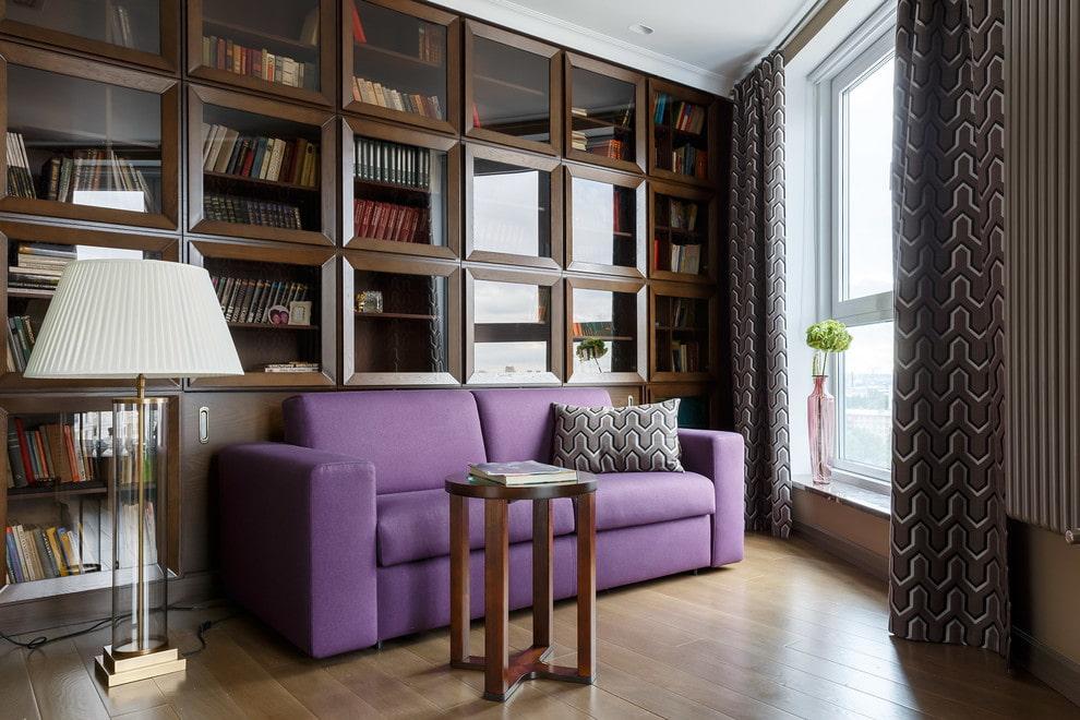 Фиолетовый диван в гостиной с домашней библиотекой