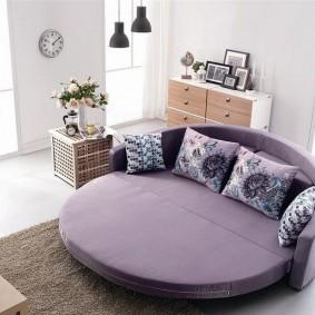 Круглый диван с фиолетовой обивкой