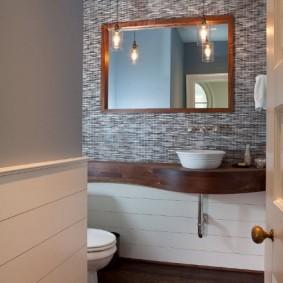 Зеркало в деревянной рамке над умывальником в ванной