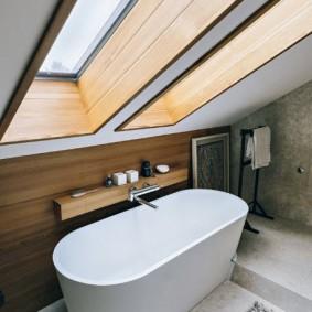 Белая ванна под окном в мансарде