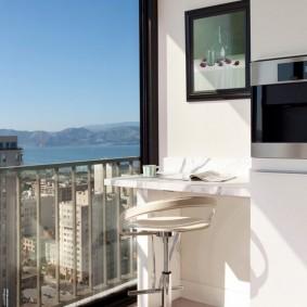 Небольшой столик у торцевой стены балкона
