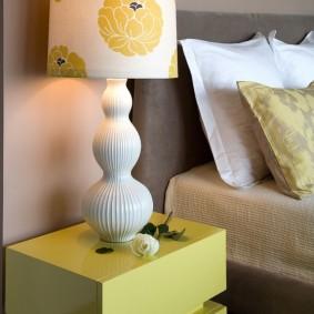 Желтая тумбочка с блестящими поверхностями
