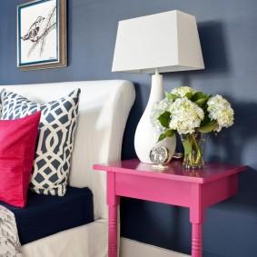 Розовый столик у кровати в спальной комнате