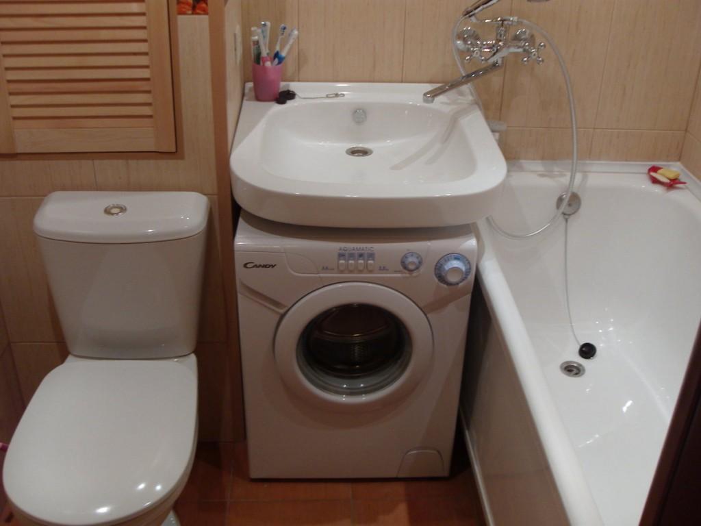Стиральная машина под фарфоровой раковиной в ванной