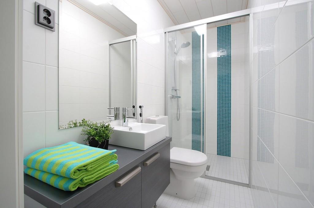 Серая тумба под раковиной в совмещенной ванной