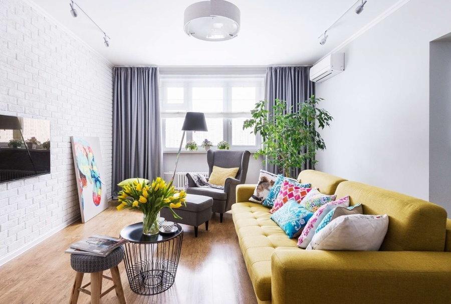 Желтый диван в гостиной с кирпичными обоями