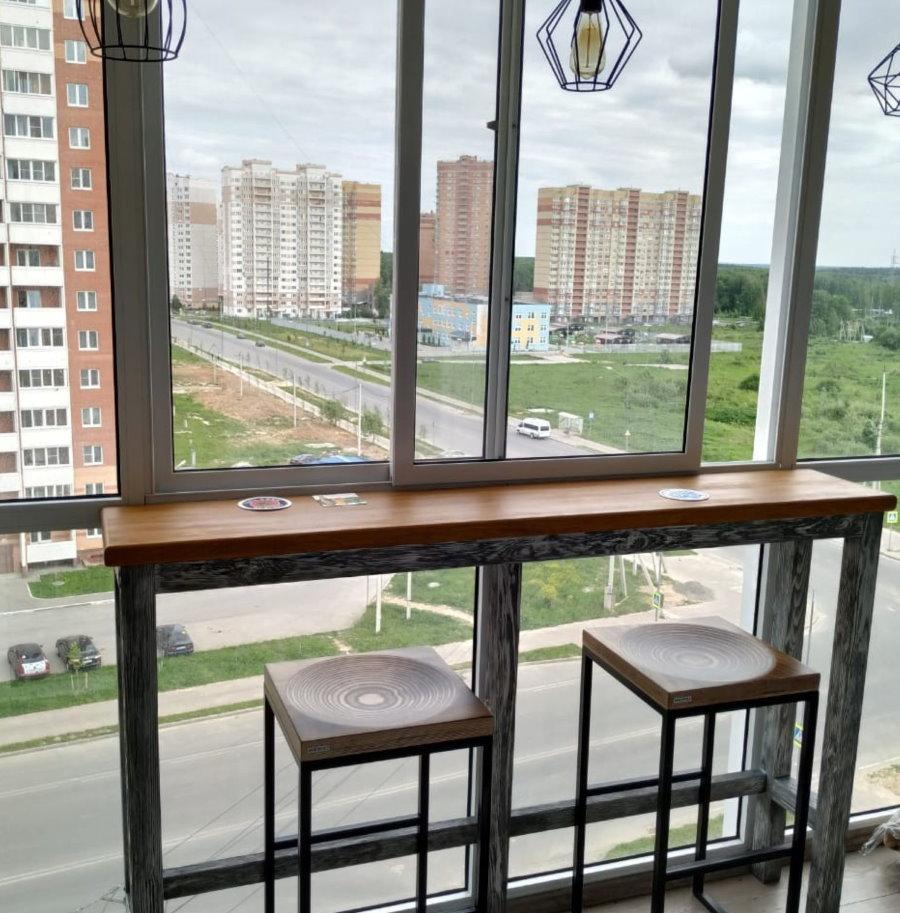 Узкая барная стойка из дерева на панорамном балконе