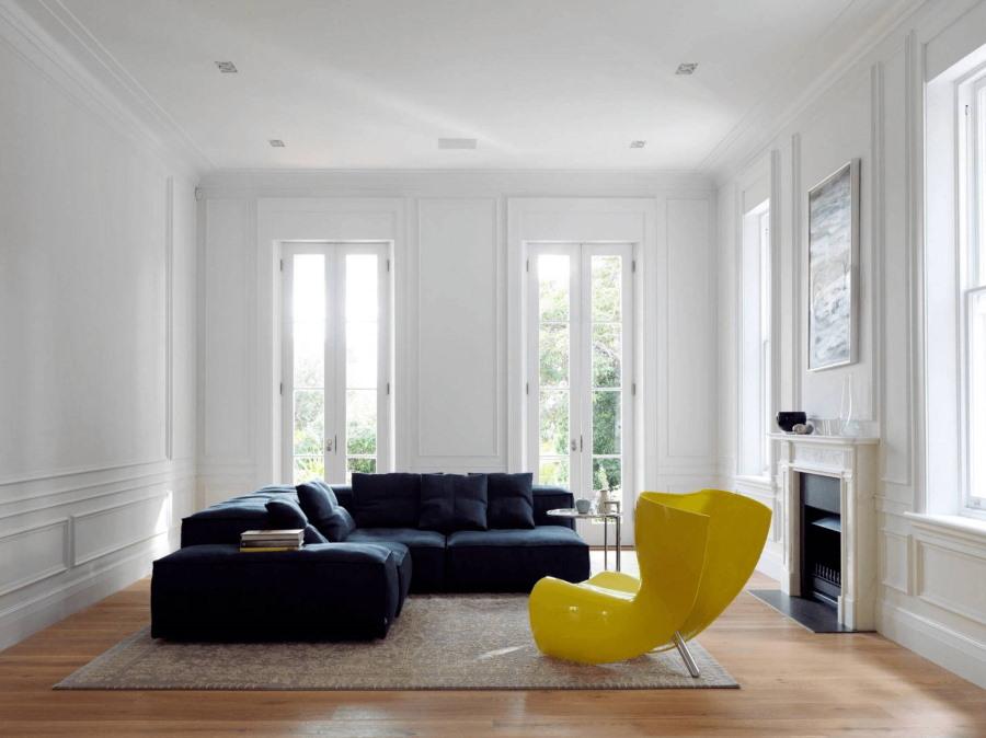 Ярко желтое кресло в белой гостиной комнате
