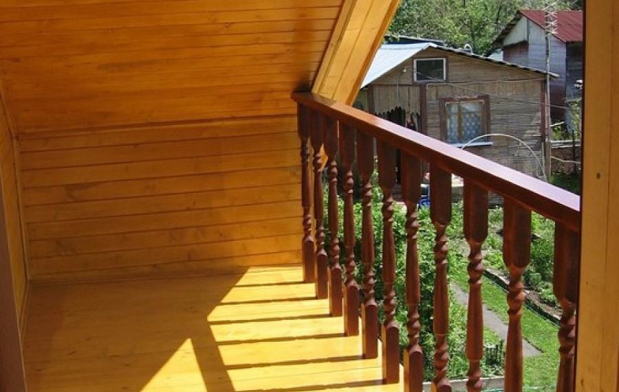 Небольшой балкон с перилами из дерева