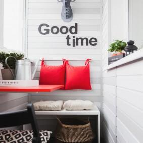 Красные подушки на белой стене балкона