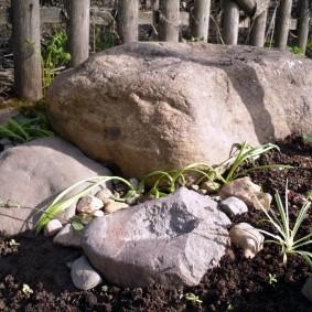 Крупные камни у садового забора
