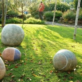 Шарообразные камни на зеленом газоне