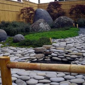 Сад камней на участке с забором из бамбука