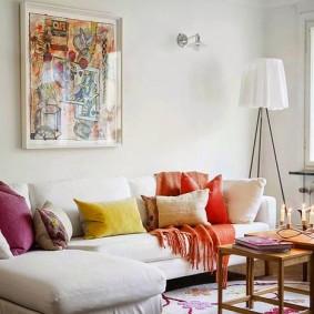 Яркие подушки на диване со светлой обивкой