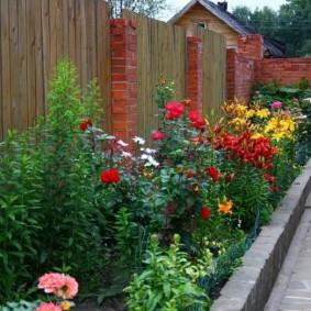 Узкий цветник перед забором из дерева