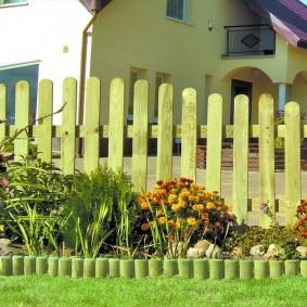 Узкая клумба с деревянным забором