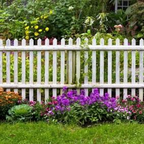 Белая ограда из деревянного штакетника