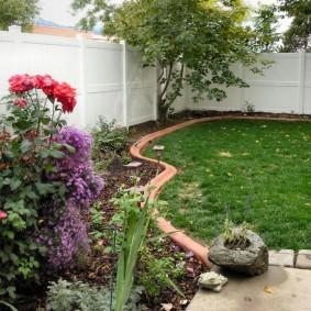 Угол садового участка с белым забором из досок