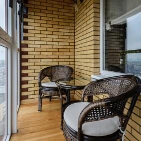 Зона отдыха на балконе с кирпичными стенами
