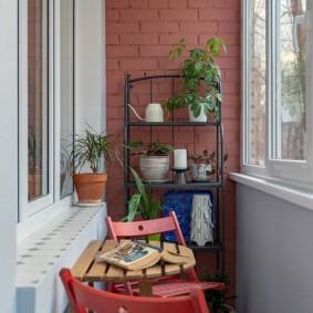 Красные стулья на балконе с рамным остеклением