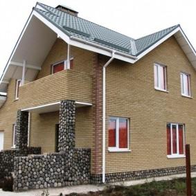 Кирпичный дом с балконом над крыльцом