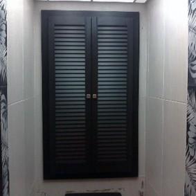Черные дверки в туалете с кафелем светлого оттенка