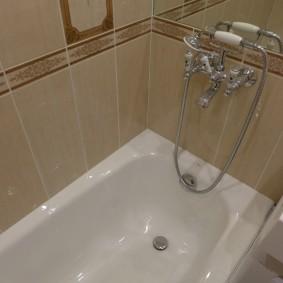 Бежевая плитка над белой ванной
