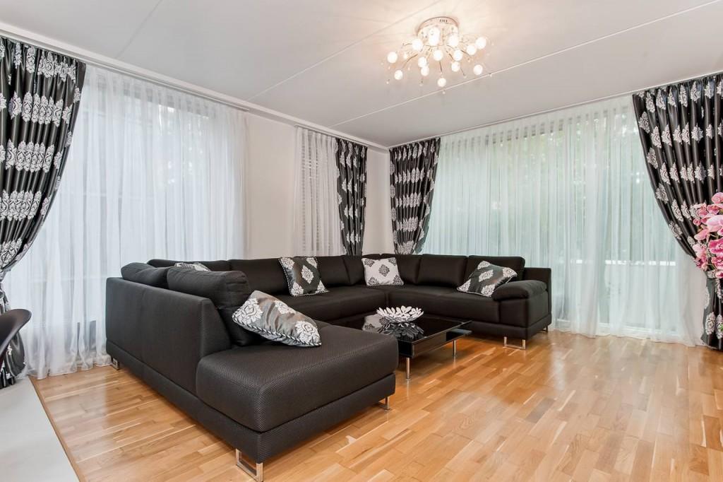 Черный диван в угловой гостиной комнате