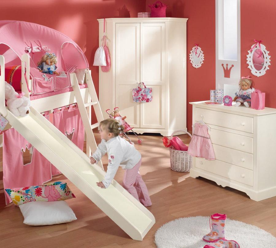 Детская кровать в комнате с розовыми стенами