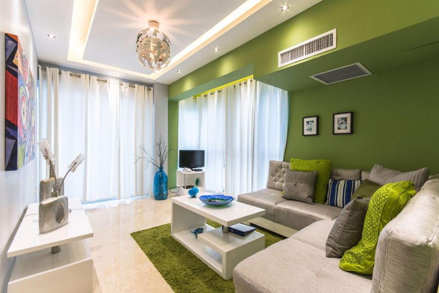 Легкие шторы белого цвета в зеленой гостиной