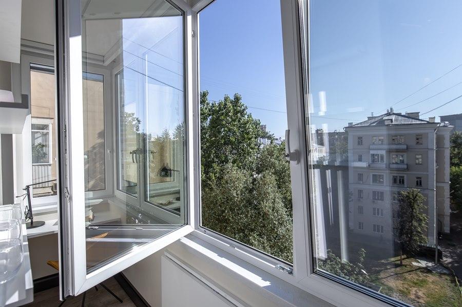 Открытая створка пластикового окна на балконе