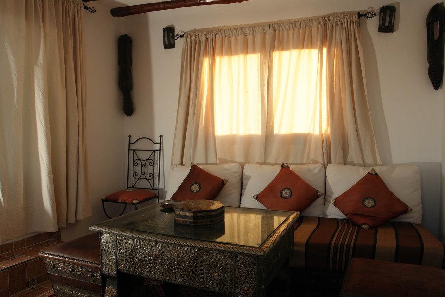 Короткие шторы в интерьере компактной гостиной