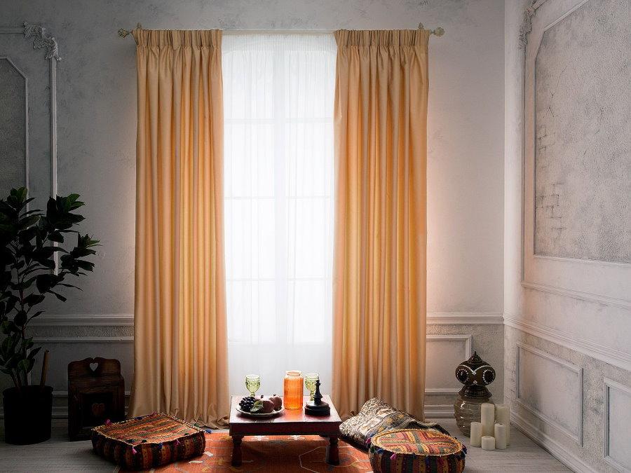 Нежно-персиковые занавески в интерьере зала