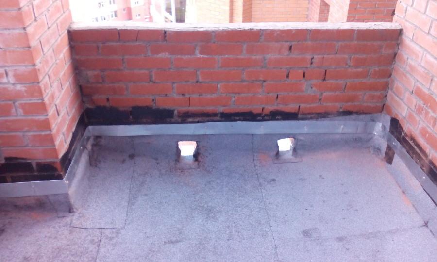 Стена кирпичного балкона с отверстиями для воды
