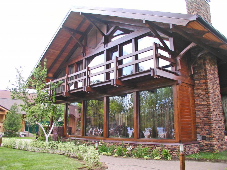 Выступающий балкон с деревянными перилами на мансарде