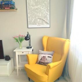 Желтое кресло на деревянных ножках