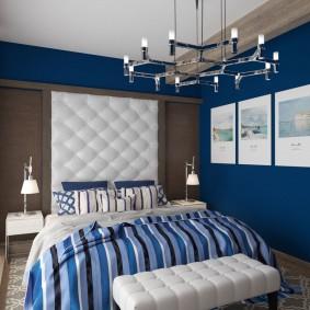 Белое изголовье кровати в спальне с обоями синего цвета