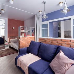 Синий диван у кирпичной полуперегородки