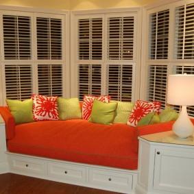Яркий диван в эркере гостиной комнаты