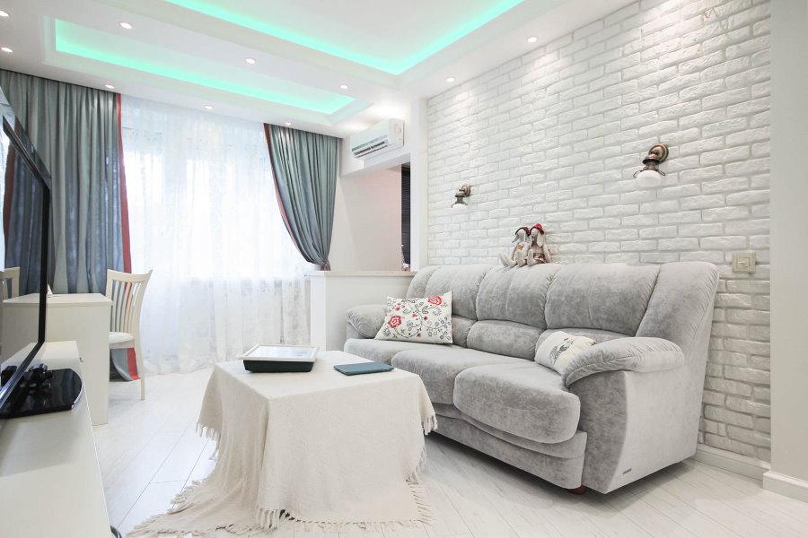 Светлая кирпичная стена за раскладным диваном