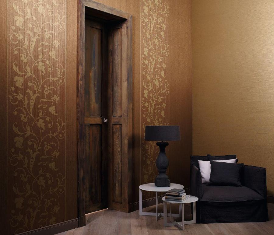 Черное кресло у стены прихожей с коричневыми обоями