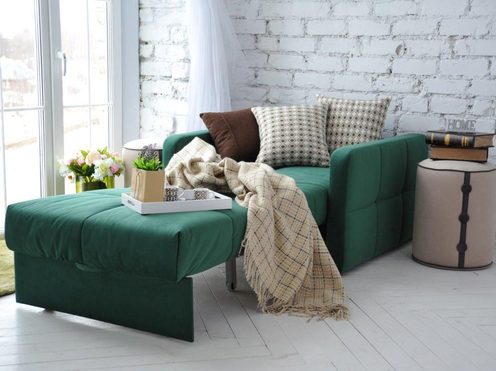 Кресло-кровать в разложенном состоянии перед окном комнаты