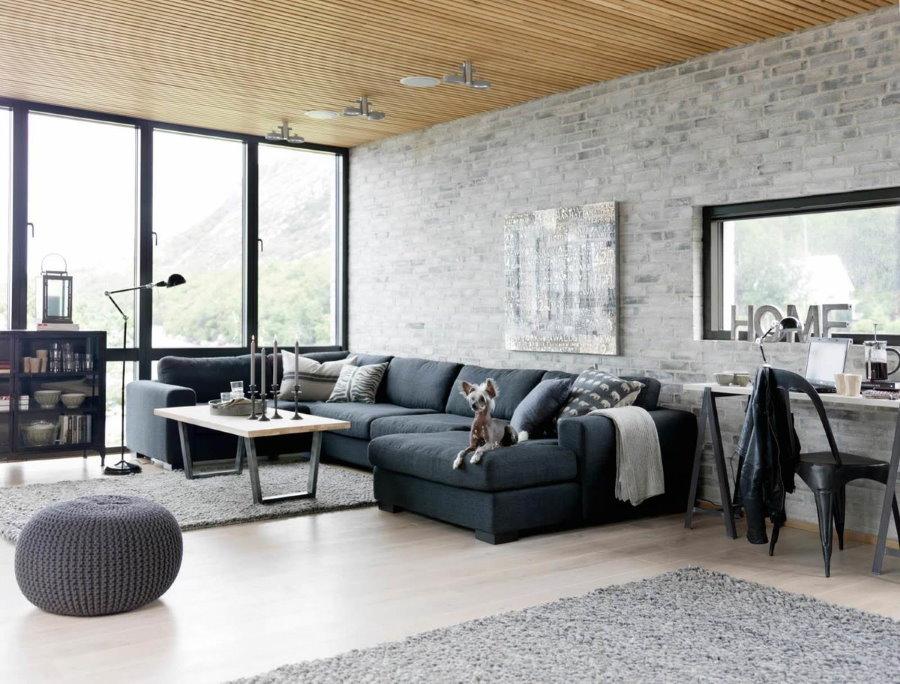 Серые кирпичные обои в комнате с деревянным потолком