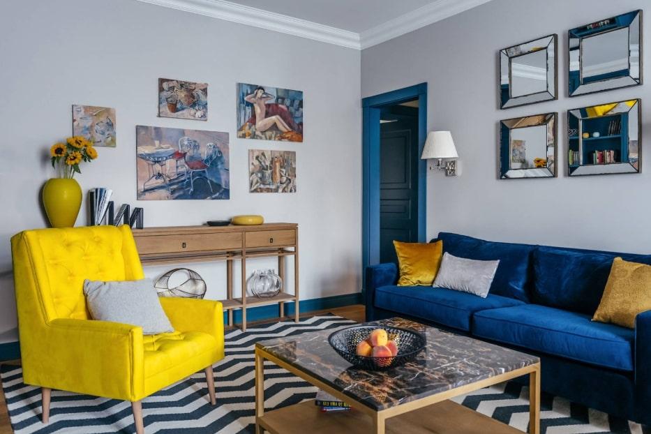 Желтое кресло напротив синего дивана в гостиной