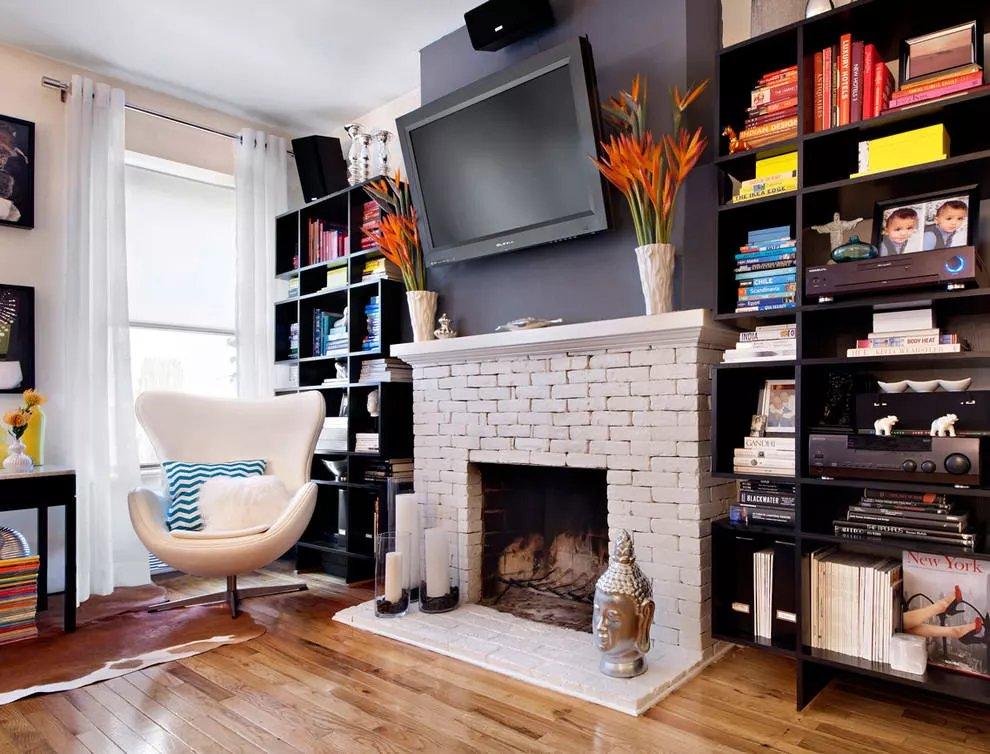 Телевизор в гостиной над декоративным камином