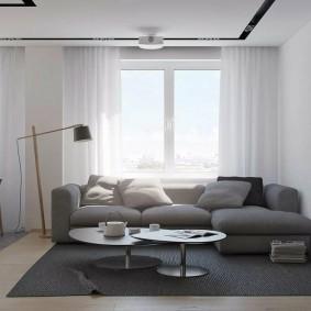 Серый ковре перед угловым диваном