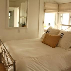 Зеркало на стене спальной комнаты