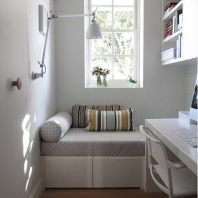Небольшой диванчик под окном маленькой комнаты