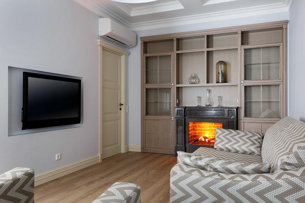Небольшая гостиная с камином и телевизором на смежных стенах