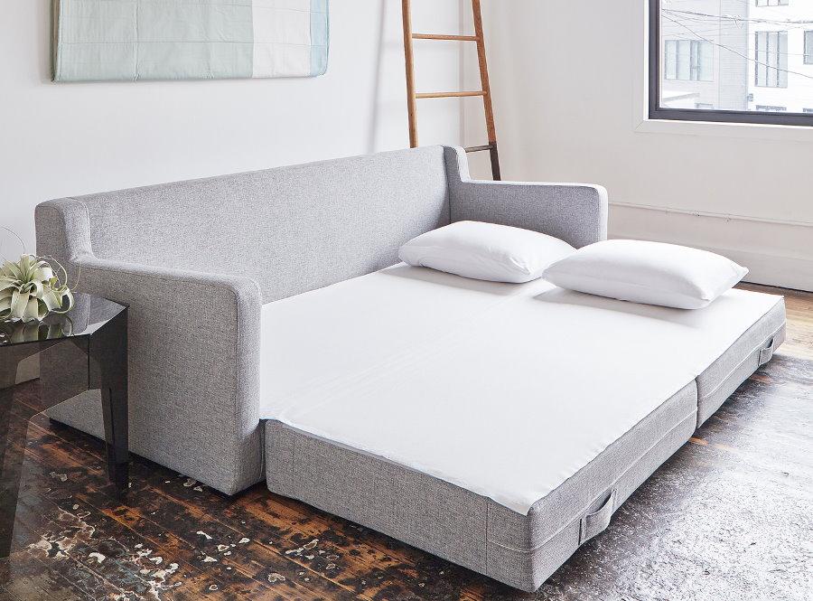 Разложенный диван в комнате без штор на окнах